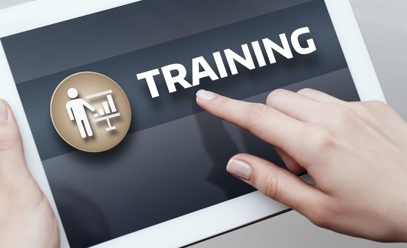 """image of person using tablet with """"Training"""" text displayed on screen"""
